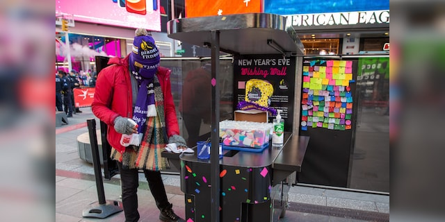 A Times Square worker disinfects a booth where people can write their New Year wish on scraps of paper that will rain at the crossroads of the world on New Year's Eve.